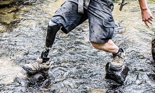 man with artificial limb crossing a creek